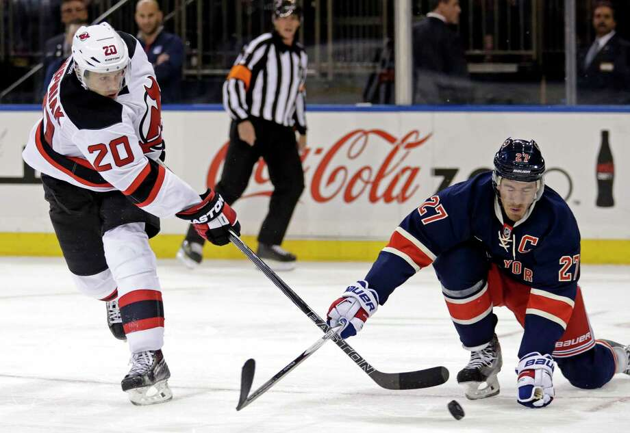 Devils right wing Lee Stempniak, left, takes a shot defended by Rangers defenseman Ryan McDonagh during the third period Sunday. Photo: Adam Hunger — The Associated Press   / FR110666 AP