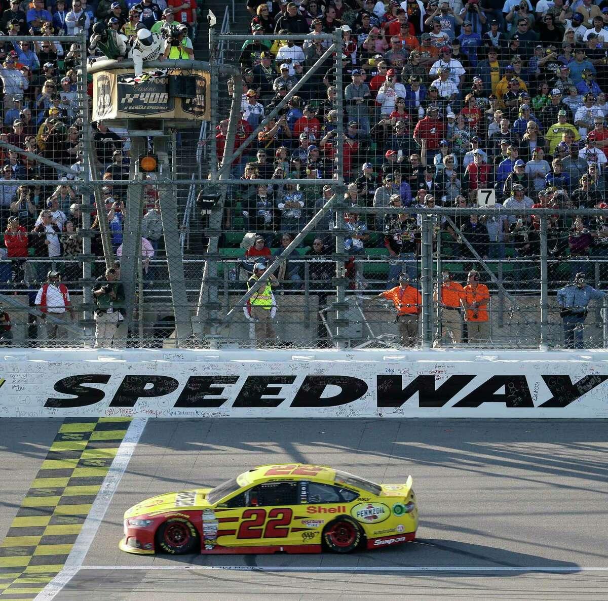 Joey Logano takes the checkered flag to win at Kansas Speedway in Kansas City, Kan., on Sunday.