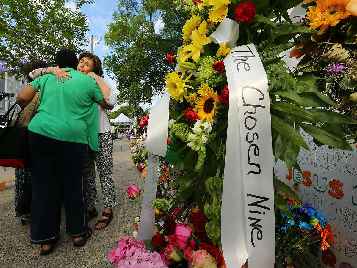Dedra Marigault, left, and Maria Bornhorst console each while visiting the sidewalk memorial in front of the Emanuel AME Church, Saturday, June 20, 2015 in Charleston, S.C. A steady stream of people brought flowers and notes and shared somber thoughts at a growing memorial in front of the church. (Curtis Compton/Atlanta Journal-Constitution via AP) MARIETTA DAILY OUT; GWINNETT DAILY POST OUT; LOCAL TELEVISION OUT; WXIA-TV OUT; WGCL-TV OUT