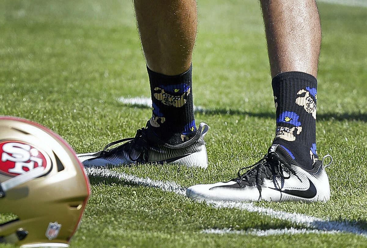 San Francisco 49ers quarterback Colin Kaepernick wears socks depicting police officers as pigs during training camp on Aug. 10 at Kezar Stadium in San Francisco.