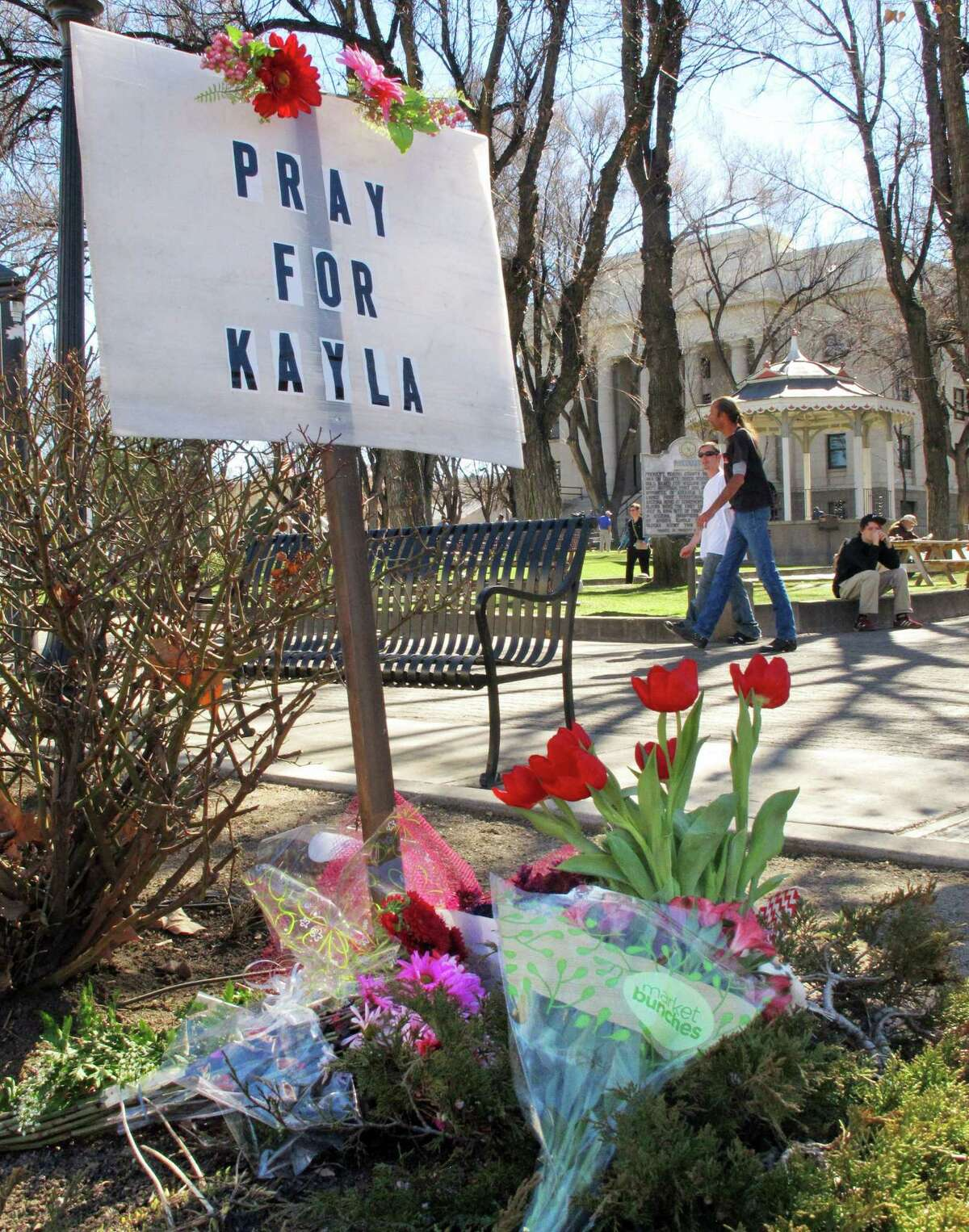 FILE -- In this Tues., Feb. 10, 2015 file photo, a small memorial honoring American hostage Kayla Mueller is on display at a corner of courthouse plaza in Prescott, Ariz. Omar Alkhani, boyfriend of Mueller, spoke to The Associated Press on Sunday, Feb. 15, 2015, via webcam from Turkey in one of his first interviews. Alkhani talked about how he met Mueller in 2010 and the last time he saw her in 2013 as a prisoner of the Islamic State group. The U.S. government and Muellerís family confirmed her death last week. (AP Photo/Felicia Fonseca, File)