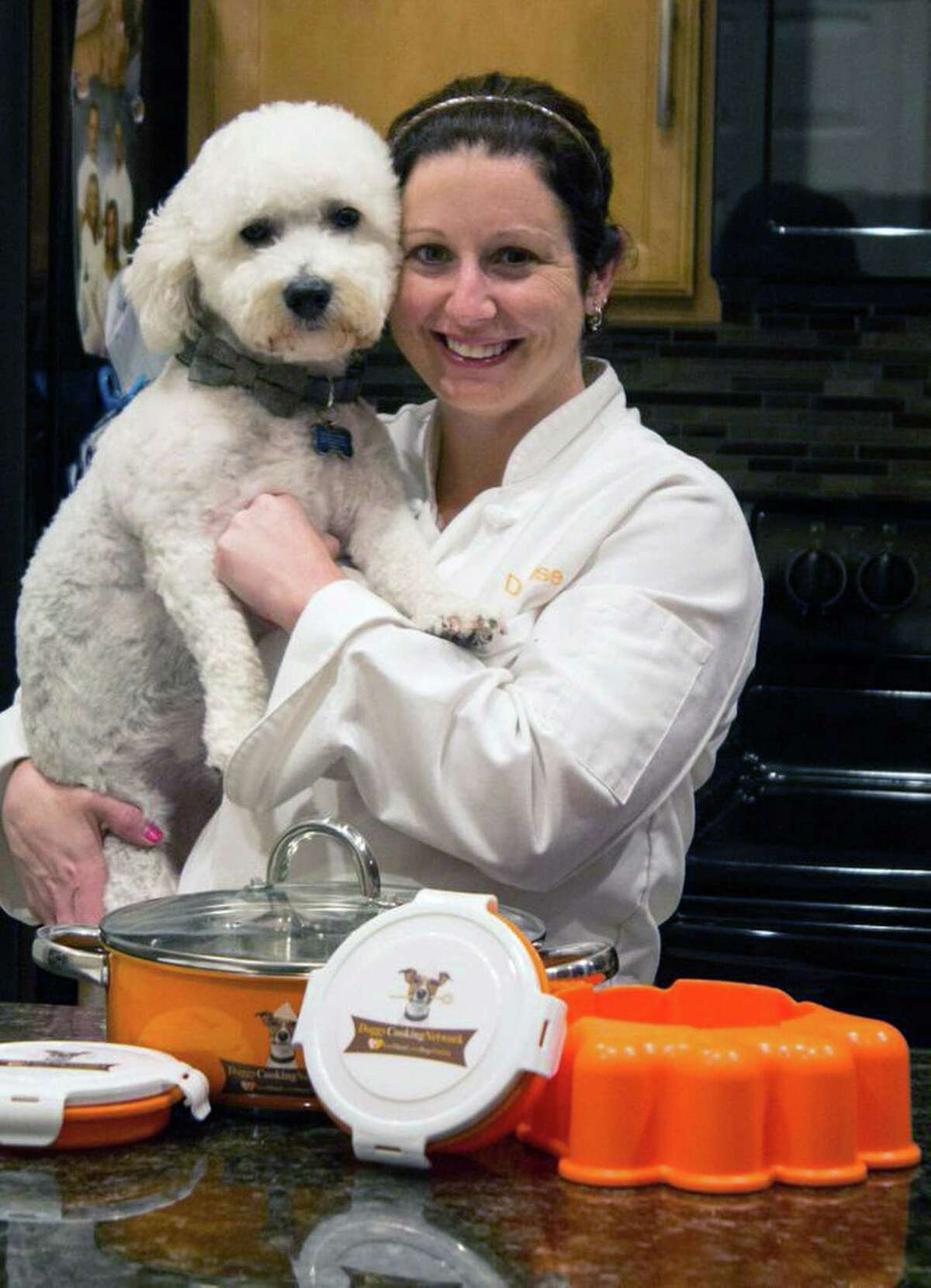 Denise Fernandez poses for a photo at the Safety Harbor, Fla., home she shares with Kris Rotondo and four dogs, including Kobe, pictured with her. The orange Pup Pot system, on the counter, is designed for cooking for the dogs and will be featured on the couple's Doggy Cooking Network on YouTube.