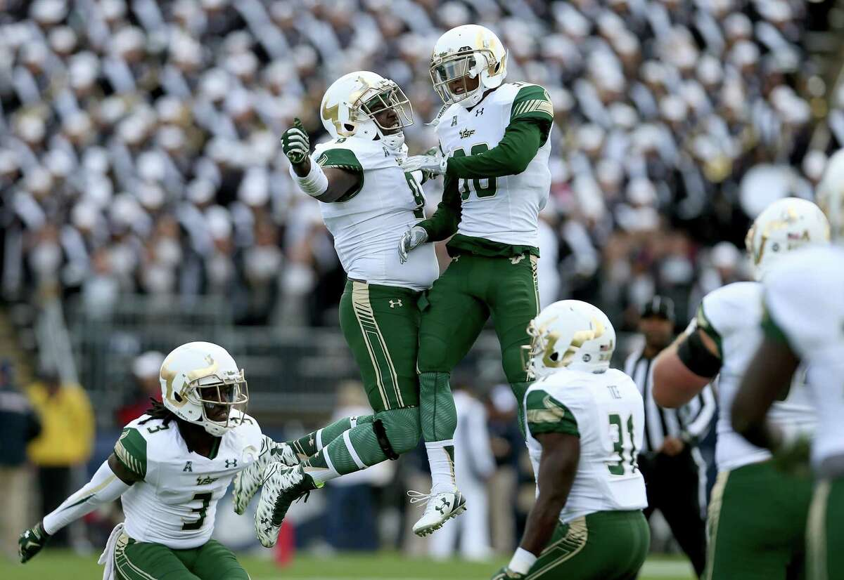 South Florida's Demetrius Hill (9) and Jalen Spencer (30) celebrate a defensive stop against UConn during the first half of the Bulls' 28-20 win on Saturday afternoon in East Hartford.