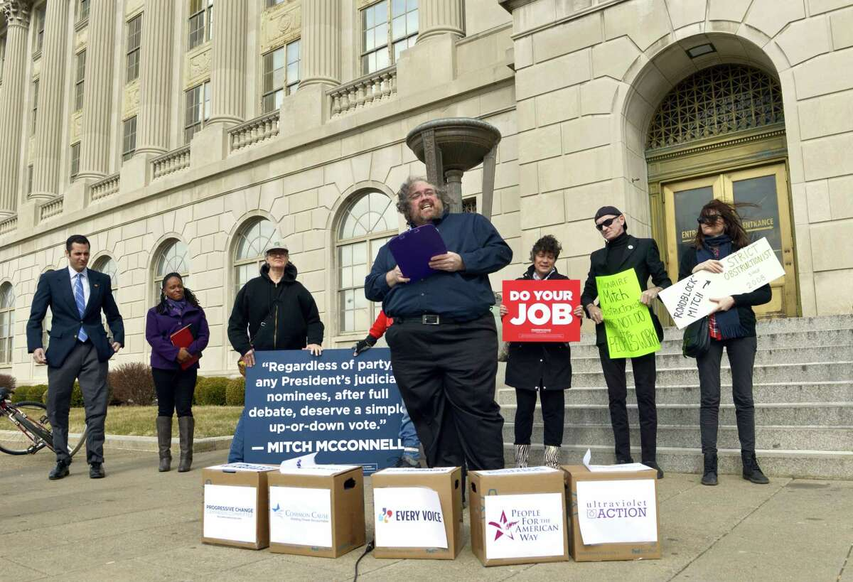 ASSOCIATED PRESS Keith Rouda, a local organizer with the Progressive Change Campaign Committee, stands in front of boxes containing signatures on petitions to be delivered to the office of U.S. Sen. Mitch McConnell, R-Ky., Friday at the federal courthouse in Louisville, Kentucky. The petitions urge Senate Republicans not to block any Supreme Court nominee by President Barack Obama.