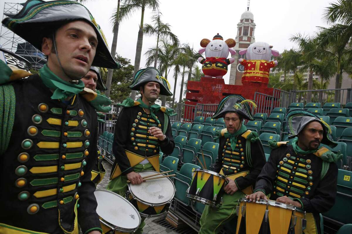 Performers from France practice in front of the sheep decorations during their rehearsal of International Chinese New Year Night Parade in Hong Kong Wednesday, Feb. 18, 2015. Decades ago the Chinese New Year holiday, also known as Spring Festival, had little impact outside of China. But as the country has gained outsized economic influence, the holiday, which has enormous cultural significance in the Chinese-speaking world, has become more prominent. (AP Photo/Kin Cheung)