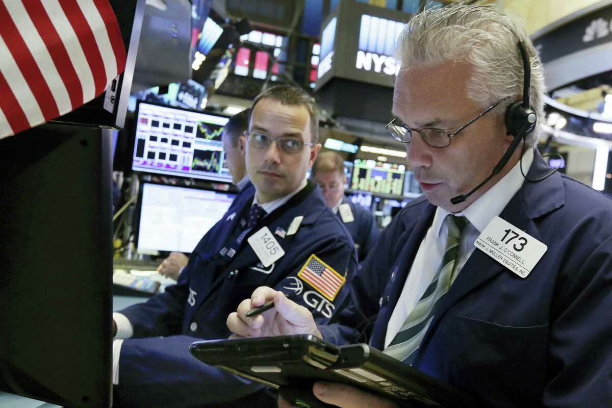 Trader Frank O'Connell, right, works on the floor of the New York Stock Exchange Thursday.