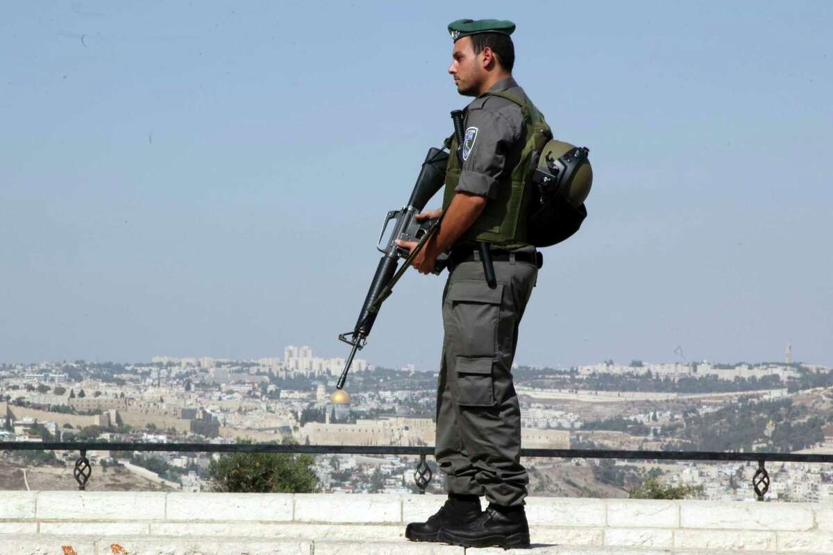 An Israeli border policeman stands on a hill overlooking Jerusalem's Old City, Saturday, Oct. 17, 2015. Palestinian assailants carried out a series of five stabbing attacks in Jerusalem and the West Bank on Saturday, as a month-long outburst of violence showed no signs of abating. The unrest came despite new security measures that have placed troops and checkpoints around Palestinian neighborhoods in east Jerusalem.