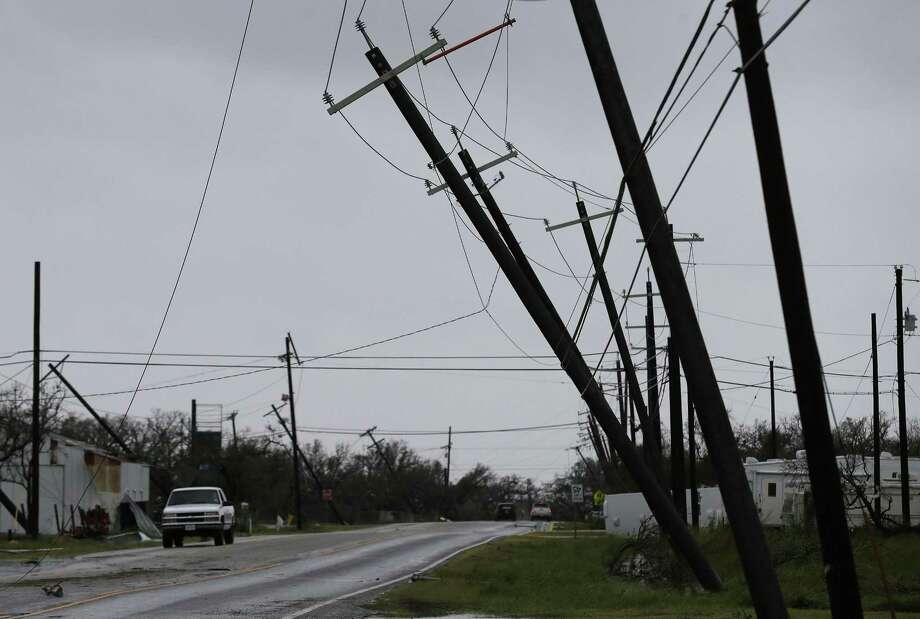 A truck drives along Market Street as utlility poles lean over the road in the aftermath of Hurricane Harvey in Rockport, Texas on Saturday, Aug. 26, 2017. (Kin Man Hui/San Antonio Express-News) Photo: Kin Man Hui, Staff / San Antonio Express-News / ©2017 San Antonio Express-News