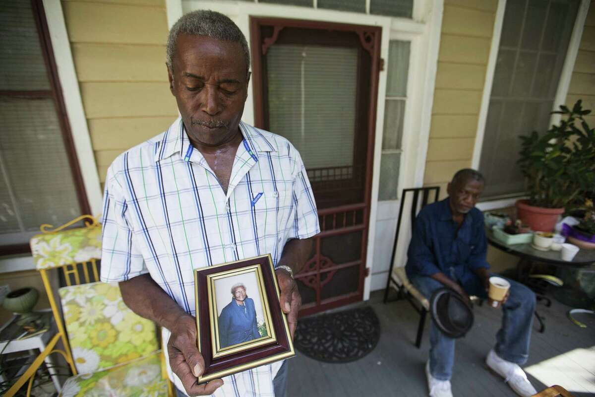 """Walter Jackson, left, holds a photo of his mother, Susie Jackson, one of the nine people killed in Wednesday's shooting at Emanuel AME Church. He was standing for a photo on his front porch as his cousin Kenneth Washington, right, looked on Friday, June 19, 2015, in Charleston, S.C. """"Right now, all in my heart is anger for him,"""" said Jackson. """"I doubt if I'll ever forgive him."""""""