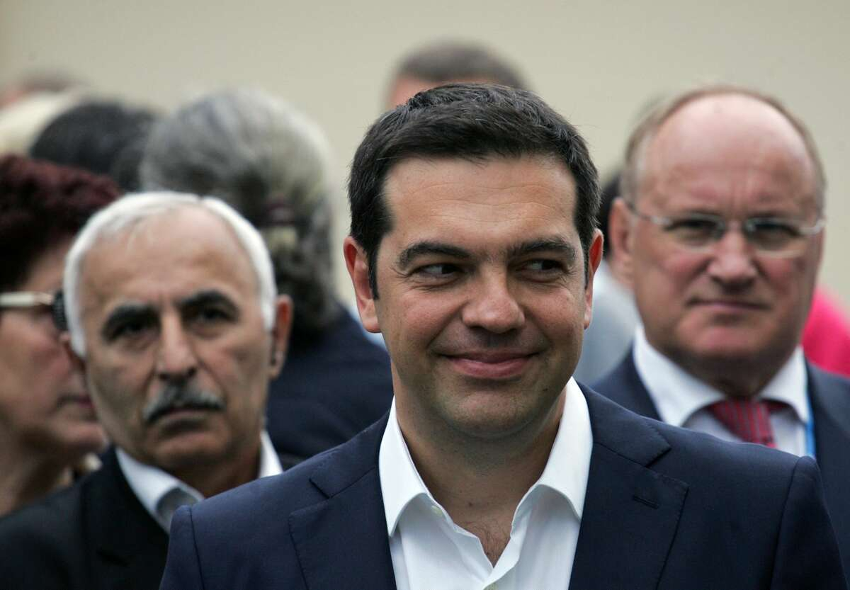 Greek Prime Minister Alexis Tsipras smiles while taking part in a wreath laying ceremony, at the monument for the founder of modern Greek state Ioannis Kapodistrias, in St. Petersburg, Russia, Friday. Russia is willing to consider giving financial aid to Greece, President Vladimir Putin's spokesman said Friday ahead of talks between the leaders of the two countries.