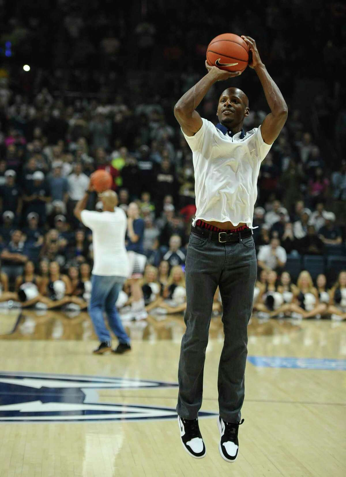 UConn legend Ray Allen competes in a 3-point competition against former Husky great Donny Marshall, background, at First Night on Friday in Storrs.
