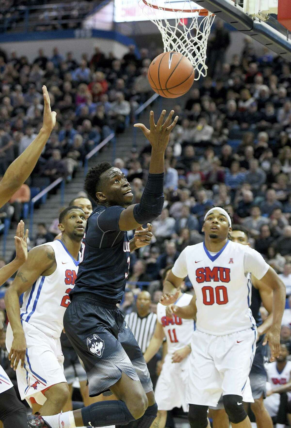 UConn's Amida Brimah (35) grabs a rebound as SMU's Ben Moore looks on during the first half Thursday.