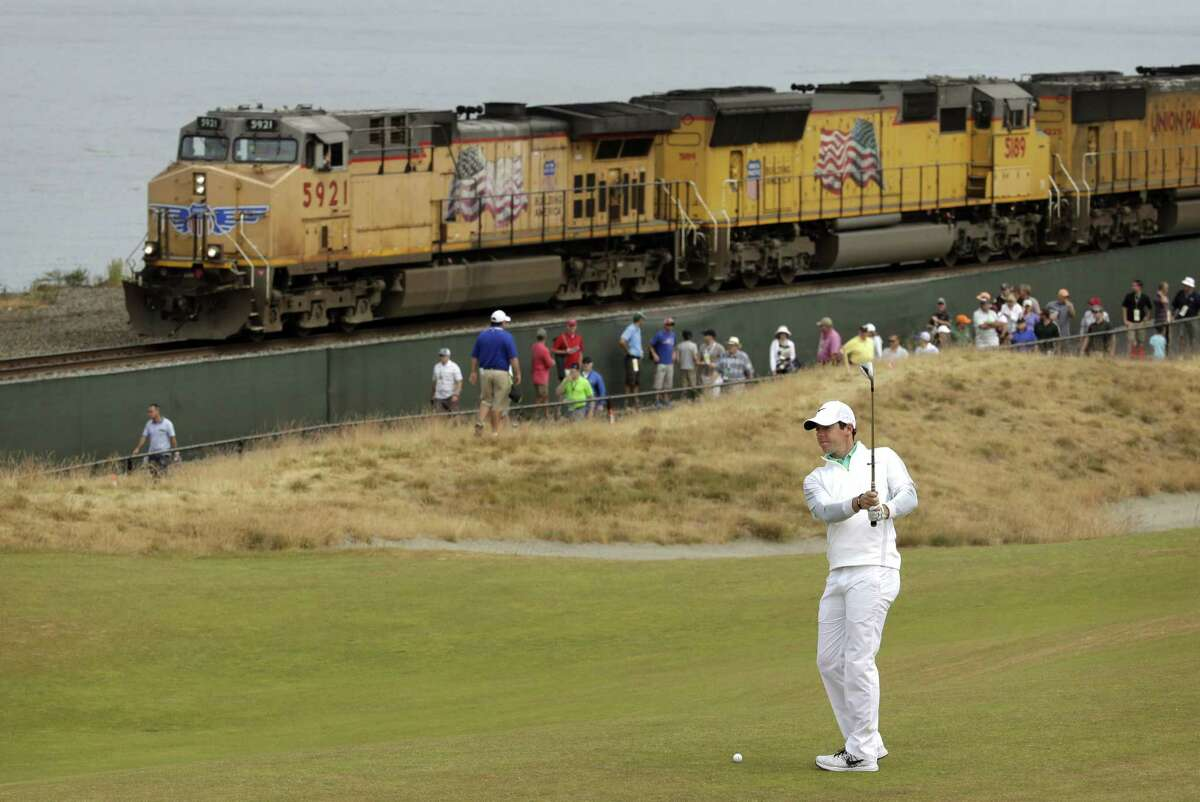 Rory McIlroy prepares to hit from the 16th fairway as a freight train rolls past during the first round of the U.S. Open Thursday at Chambers Bay in University Place, Wash.
