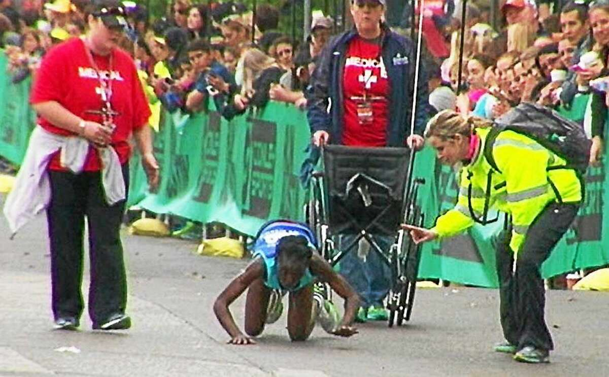 Austin Marathon volunteers rush to help elite runner Hyvon Ngetich after she collapsed to her knees near the finish line of the weekend race. Ngetich refused help and crawled across the finish line, taking third place.