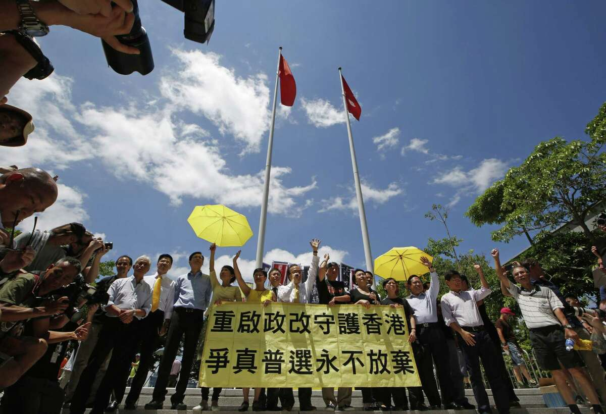 Pro-democracy lawmakers celebrate outside the Legislative Council in Hong Kong, Thursday, June 18, 2015. The Hong Kong government's controversial Beijing-backed election reforms were defeated Thursday by pro-democracy lawmakers. (AP Photo/Kin Cheung)