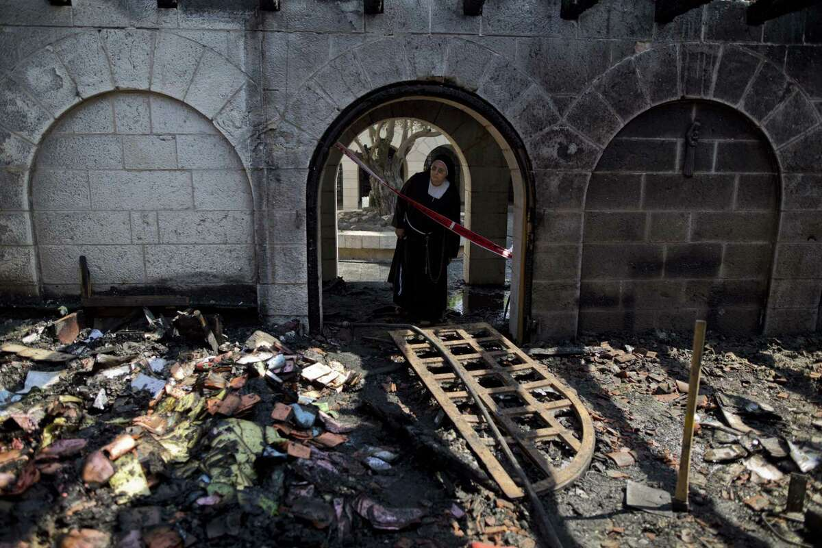 A nun looks at a heavily damaged Church of Multiplication after a fire broke out overnight near the Sea of Galilee in Tabgha, Israel, Thursday, June 18, 2015. Israel police spokesman Micky Rosenfeld said police are investigating whether the fire was deliberate and are searching for suspects. A passage from a Jewish prayer, calling for the wiping out of idol worship, was found scrawled in red spray paint on a wall outside the Catholic church. (AP Photo/Ariel Schalit)