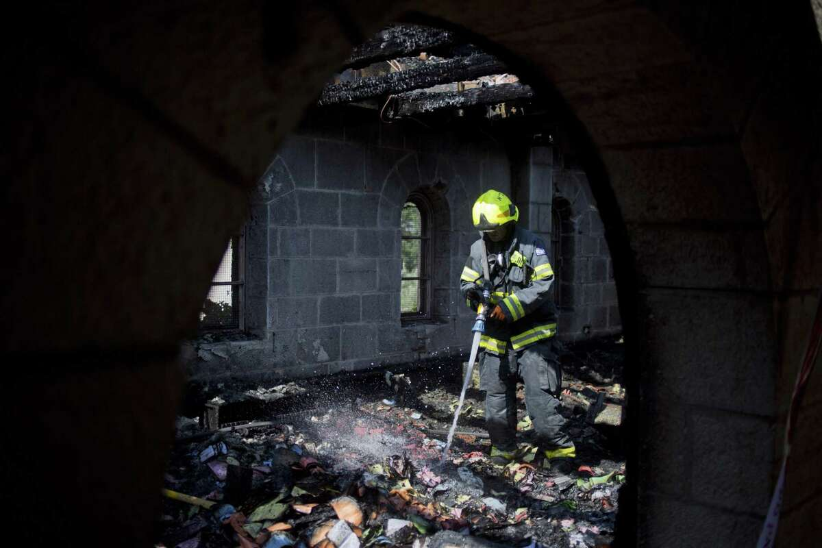 An Israeli fire fighter works at the site of a fire that caused heavy damage to the Church of Multiplication near the Sea of Galilee in Tabgha, Israel, Thursday, June 18, 2015. Israel police spokesman Micky Rosenfeld said police are investigating whether the fire was deliberate and are searching for suspects. A passage from a Jewish prayer, calling for the wiping out of idol worship, was found scrawled in red spray paint on a wall outside the Catholic church. (AP Photo/Ariel Schalit)