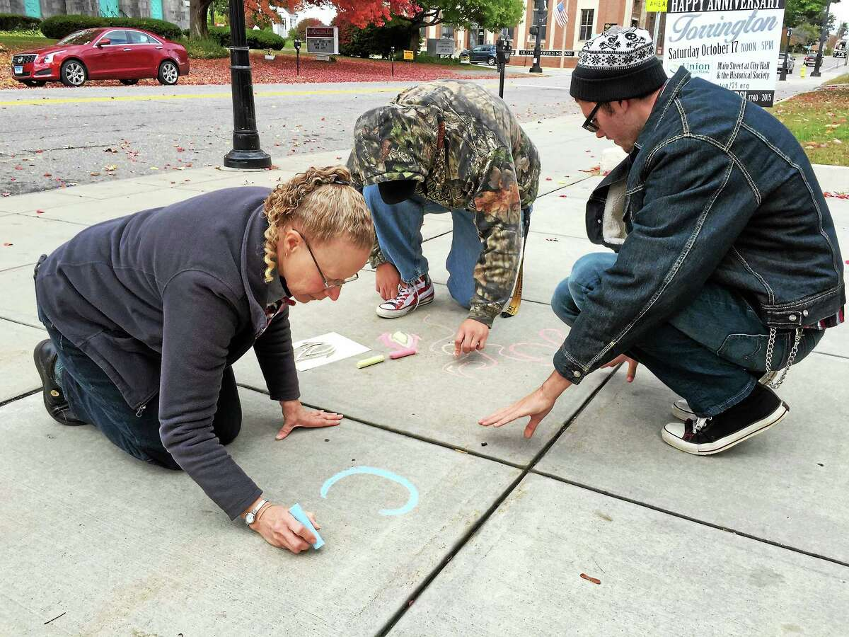 Members and administrators of the Highlander Transition Academy chalked messages and drawings about fire safety on city streets Friday morning.