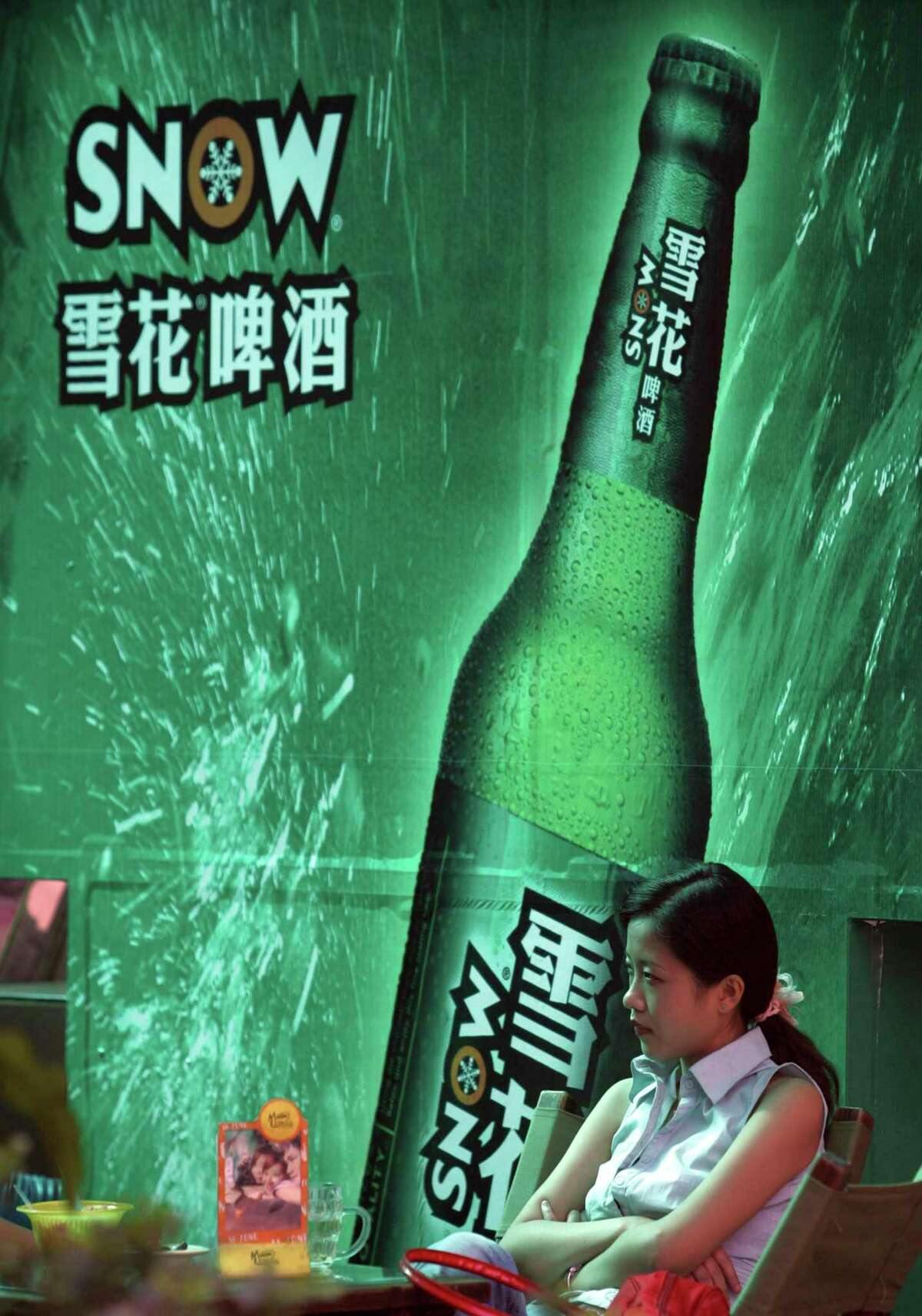 In this Sept. 11, 2006, photo, a woman sits near an advertising poster for Snow Beer in a bar in southwestern China's Chongqing municipality. A potential prize for AB InBev in its bid for SABMiller is a Chinese beer, Snow, that is the world's biggest seller. But any deal will face Chinese regulators who have barred the two brewing giants in the past from cooperating.
