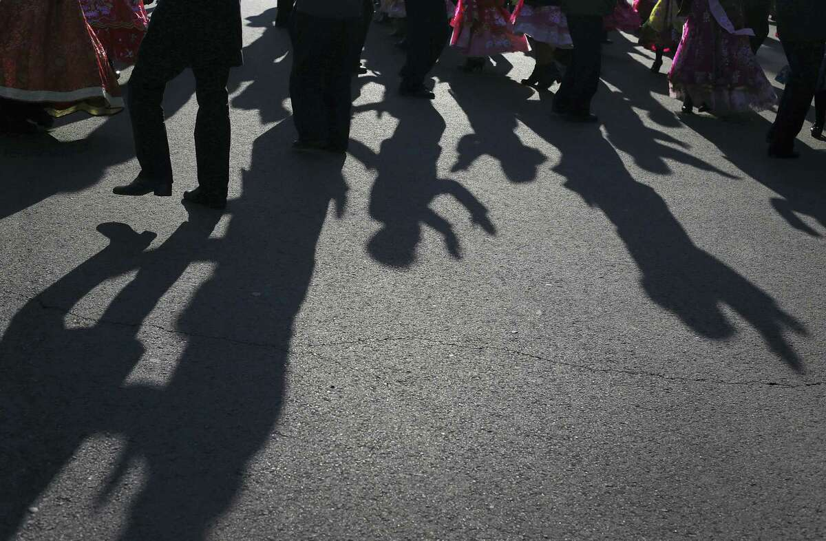 """The shadows of North Korean men and women are cast on the grounds of the Pyongyang Indoor Stadium as they participate in a mass dance party as part of celebrations of the """"Day of the Shining Star"""" or birthday anniversary of late North Korean leader Kim Jong Il on Tuesday, Feb. 16, 2016, in Pyongyang, North Korea. The celebrations of the Kim's birthday anniversary, a revered national holiday, came as South Korea's president warned that North Korea faces collapse if it doesn't abandon its nuclear weapons program, amid an international outcry over Pyongyang's January nuclear test and the Feb. 7 rocket launch."""