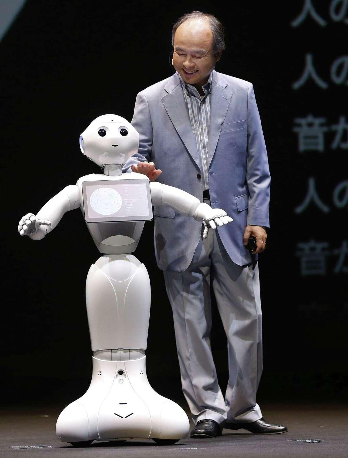 El presidente de la empresa SoftBank Masayoshi Son saluda al robot Pepper, que la compaÒÌa presentÛ cerca de Tokio el jueves 18 de junio de 2015. (Foto AP/Shizuo Kambayashi)
