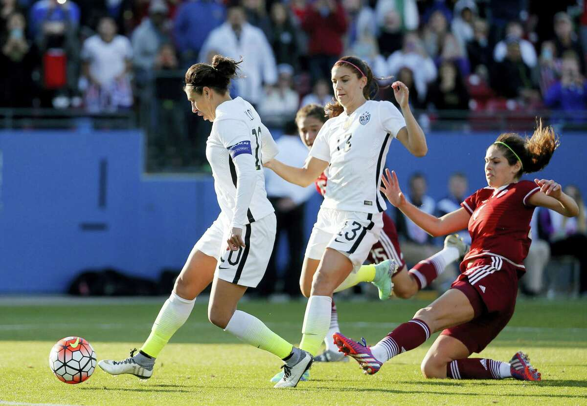 United States midfielder Carli Lloyd (10) scores off her own rebound following an attempted penalty kick against Mexico in the second half of a CONCACAF Olympic qualifying tournament soccer match, Saturday, Feb. 13, 2016, in Frisco, Texas. The U.S.' Alex Morgan (13) and Mexico' Alina Garciamendez (4) watch on the play. The U.S. won 1-0. (AP Photo/Tony Gutierrez)