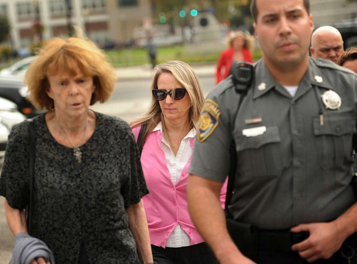 In this Tuesday, Oct. 13, 2015, photo, Jennifer Connell, center, is escorted to her car by marshals after her lawsuit against her Westport nephew was found in his favor in Superior Court in Bridgeport, Conn. She sued her nephew, who was eight-years-old at the time of the incident, for breaking her wrist after jumping into her arms at his birthday party.