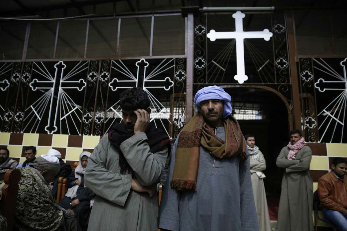Men mourn over the Egyptian Coptic Christians who were captured in Libya and killed by militants affiliated with the Islamic State group, at the Virgin Mary church in the village of el-Aour, near Minya, 220 kilometers (135 miles) south of Cairo, Egypt, Monday, Feb. 16, 2015. Egyptian warplanes struck Islamic State targets in Libya on Monday in swift retribution for the extremists' beheading of a group of Egyptian Christian hostages on a beach, shown in a grisly online video released hours earlier.