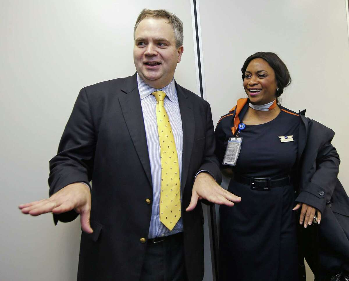 In this Feb. 5, 2015 photo, JetBlue's incoming CEO Robin Hayes, left, gestures while sharing a laugh with a JetBlue flight attendant at JFK airport in New York.