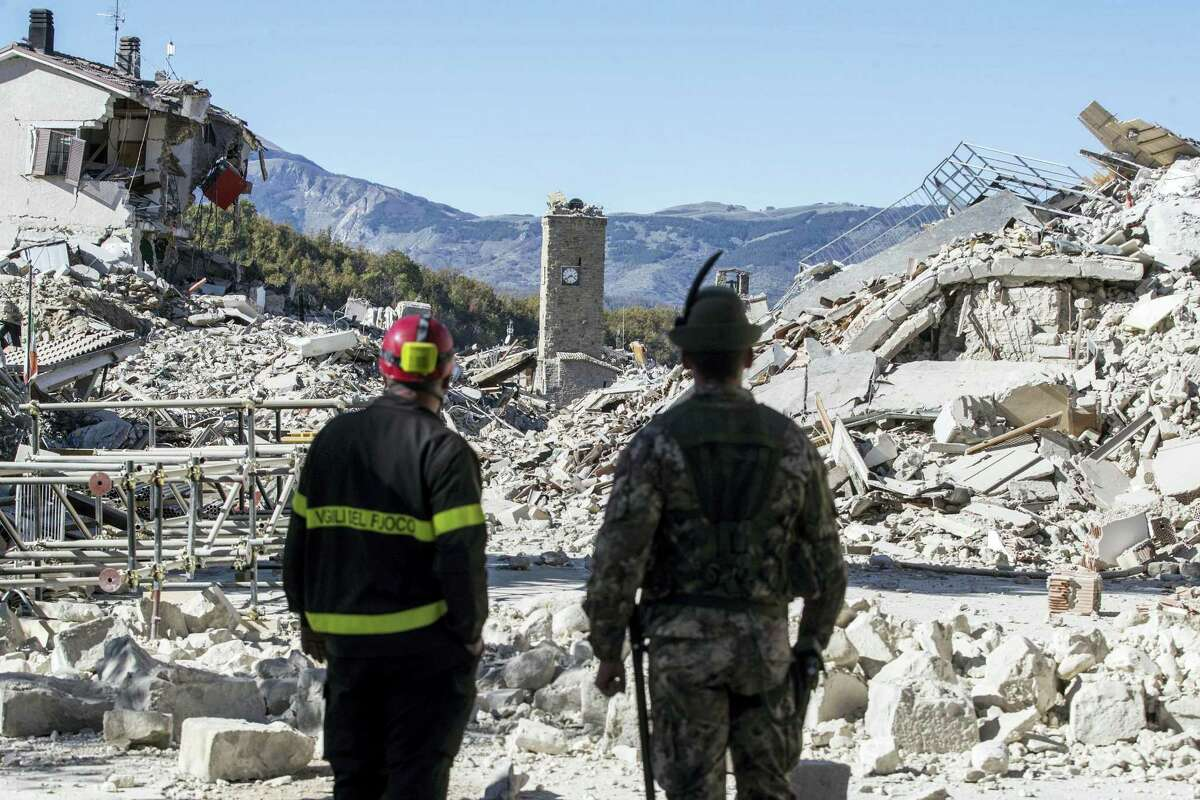 A firefighter, left, and an alpine soldier look at rubble in the hilltop town of Amatrice as an earthquake with a preliminary magnitude of 6.6 struck central Italy on Oct. 30, 2016. A powerful earthquake rocked the same area of central and southern Italy hit by quake in August and a pair of aftershocks last week, sending already quake-damaged buildings crumbling after a week of temblors that have left thousands homeless.