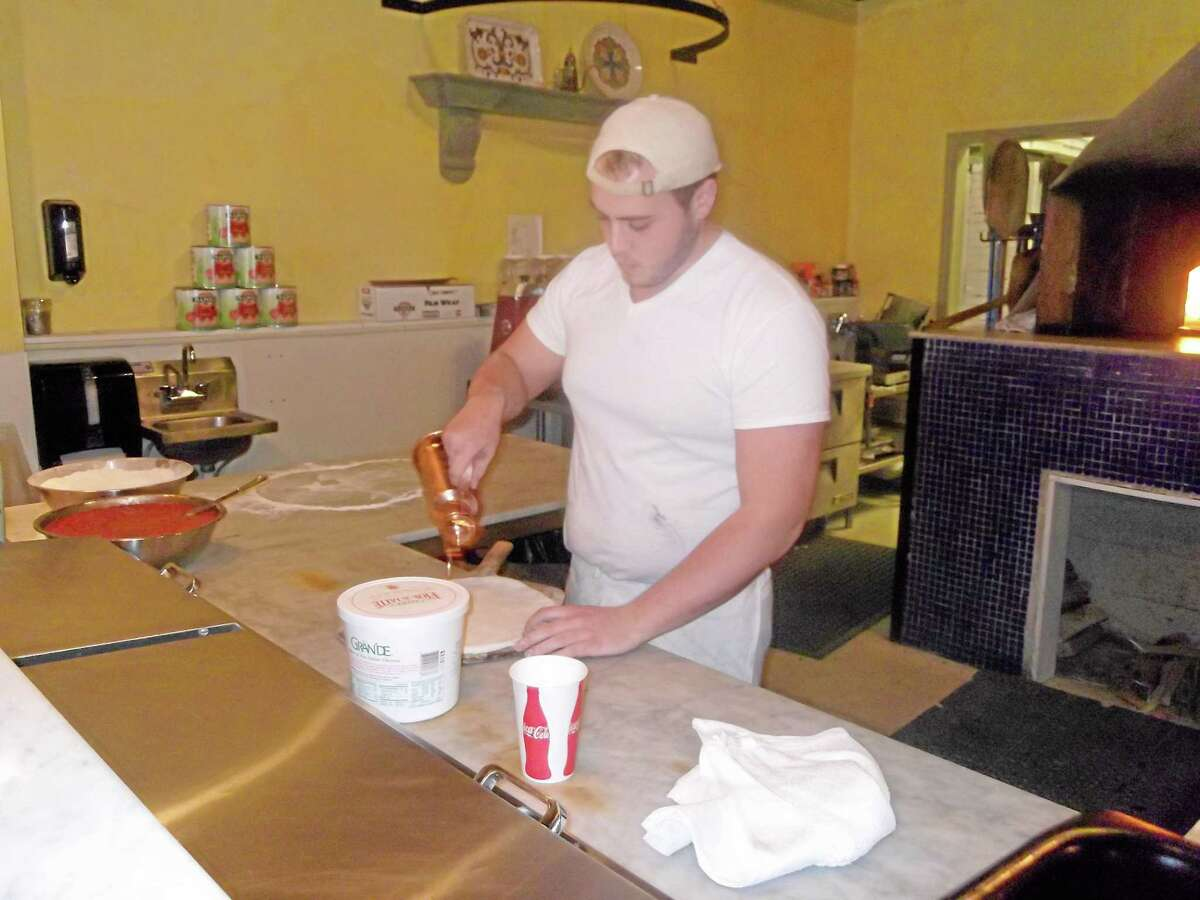 Robert Bayette, manager of Pizzeria Marzano on East Main Street in Torrington, makes a pizza.
