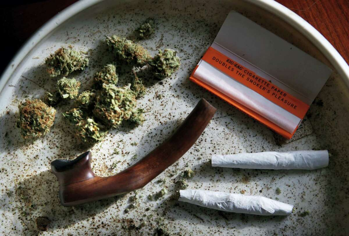 This this Nov. 21, 2014 photo shows medical marijuana, a pipe, rolling papers and two joints in Belfast, Maine. Advocates for legalizing recreational marijuana are looking to score their first significant electoral victories in eastern U.S. states on Nov. 8, 2016. Massachusetts and Maine are among five states, joining California, Arizona and Nevada, where legalization questions are before voters.