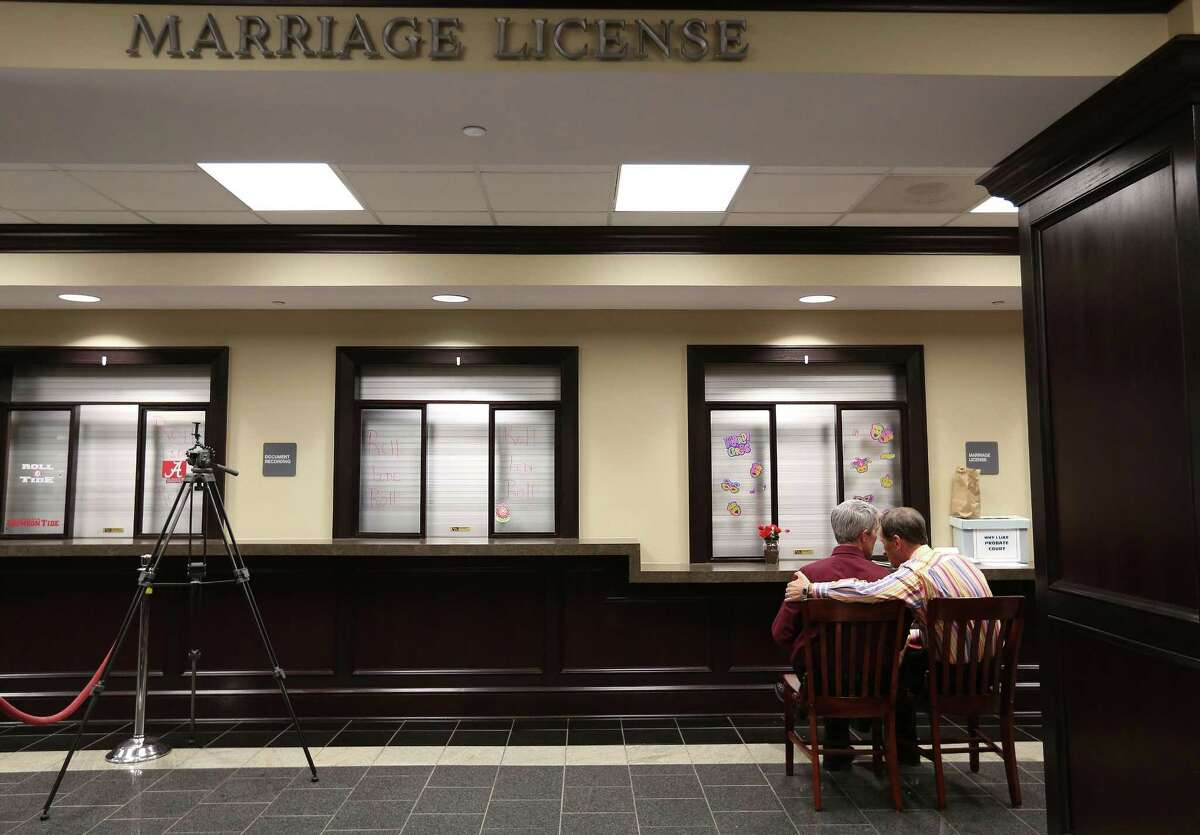 Milton Persinger, left, and Robert Povilat wait for a marriage license at the Mobile County Probate office in Mobile, Ala.