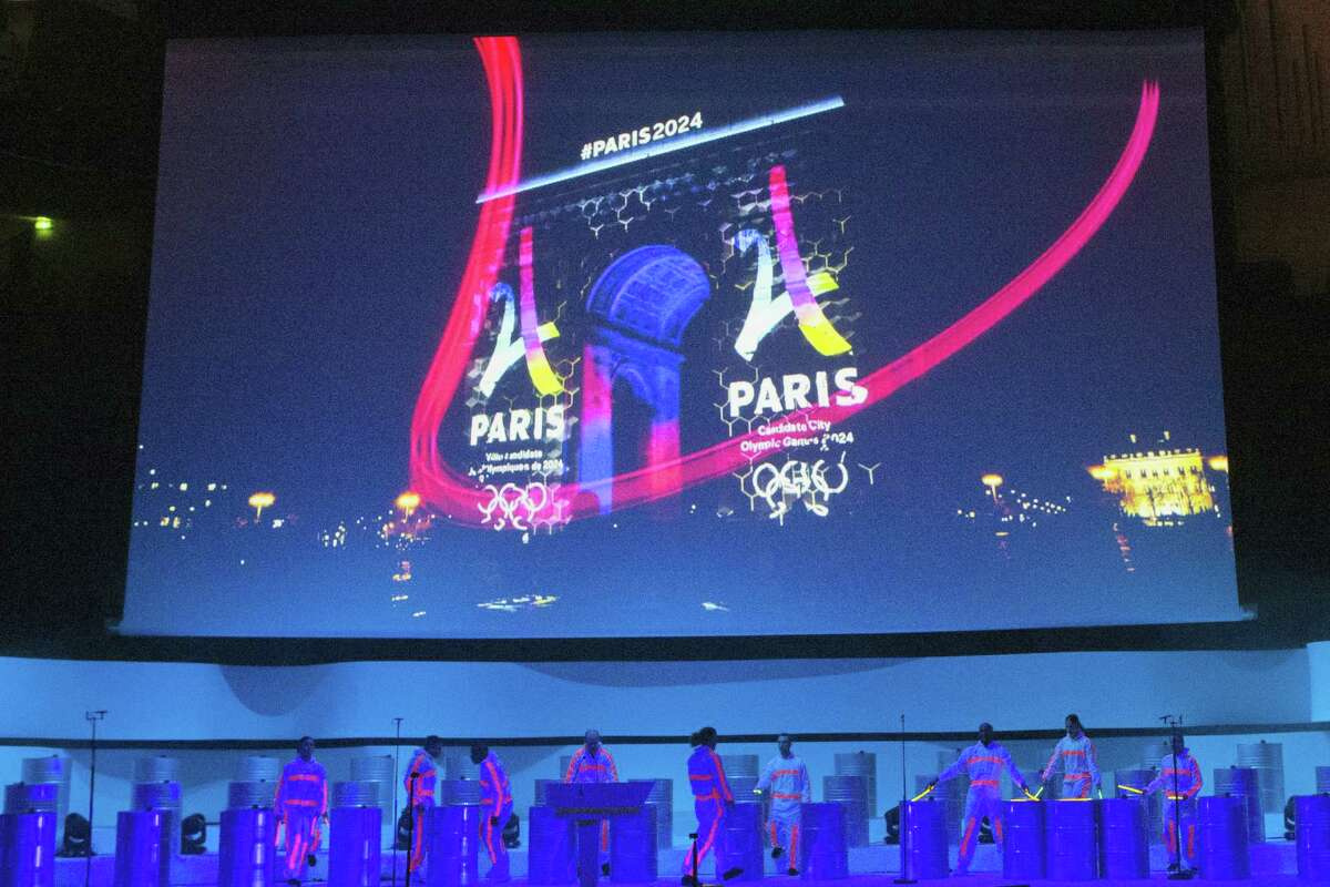 Dancers perform on stage as the Eiffel Tower-shaped bid logo for the Paris 2024 is projected on the Arc de Triomphe on a giant screen during the official presentation of Paris as candidate for the 2024 Olympic summer games in Paris, France, Wednesday, Feb. 17, 2016. Paris, which hosted the Olympics in 1900 and 1924, is competing against Budapest, Rome and Los Angeles for the games. The International Olympic Committee will choose the host city in September 2017.
