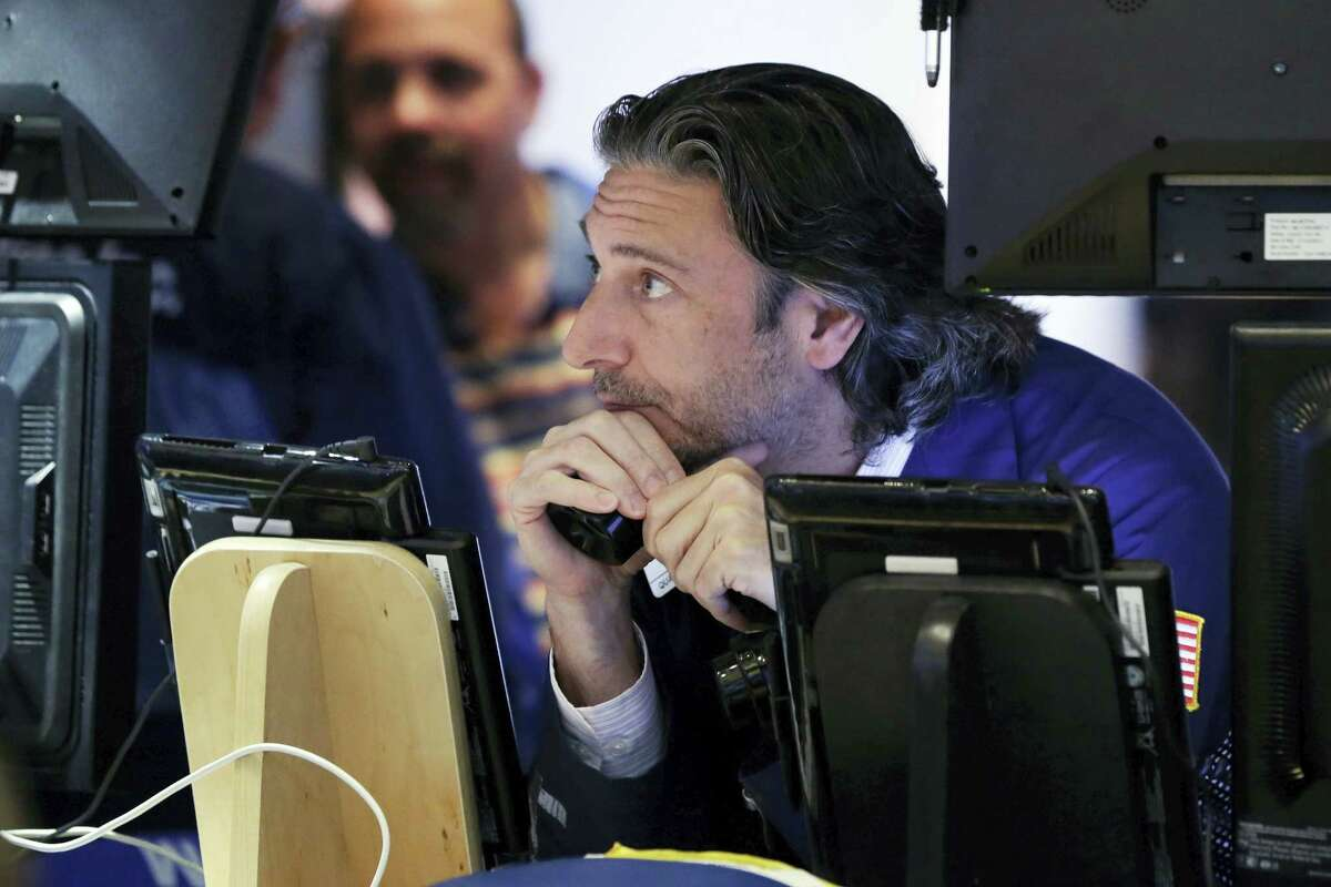 In this June 24, 2016 photo, trader John Romolo works on the floor of the New York Stock Exchange. The U.K.'s vote to leave the European Union has caused trillions of dollars in wealth to evaporate.