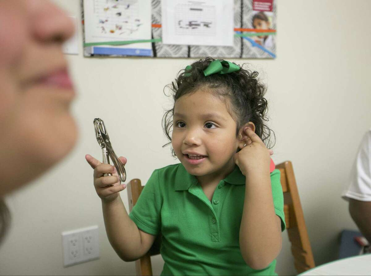"""Angelica Lopez, 3, who is the recipient of an Auditory Brainstem Implant (ABI) holds a single-hole punch to help mark the sound of the word """"punch,"""" as she receives oral recovery therapy from Debra Schader, an educational specialist at the USC-CHLA Center for Childhood Communication in Los Angeles."""