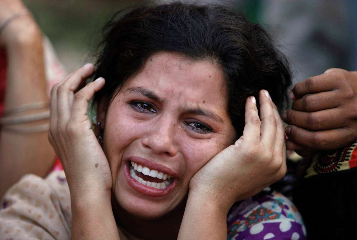 A woman mourns the death of her daughter, a victim of landslide, in Karachi, Pakistan, Tuesday, Oct. 13, 2015. Police say a landslide has hit three makeshift homes in a slum, killing more than a dozen people. Senior police officer Javed Jaskani says the incident took place early Tuesday when a mass of mud and rocks crashed down a hill into camps in Karachi, the capital of southern Sindh province. He says women and children were among the dead and injured.