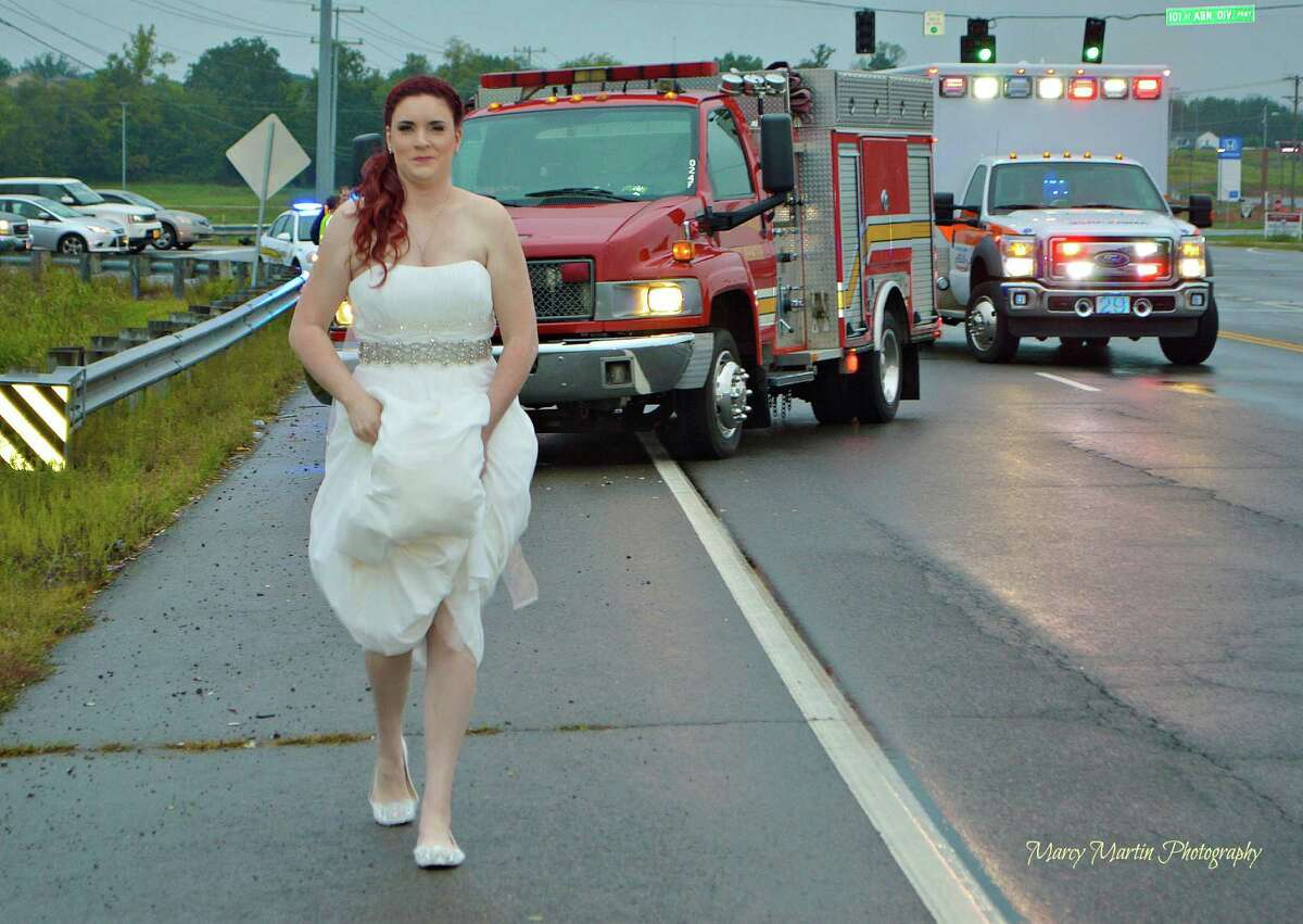 In this Oct. 3, 2015 photo provided by Marcy Martin Photography, her daughter Sarah Ray, in her wedding dress, attends to a car crash in Clarksville, Tenn. Ray's father and grandparents where in a car crash on their way to Ray's wedding reception. Ray, who is a paramedic, went to the scene to check on her relatives.