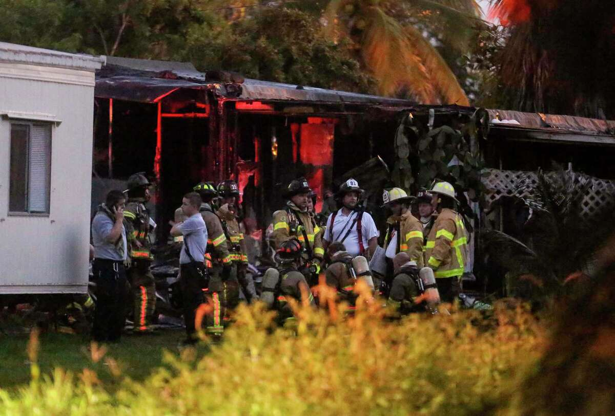 Firefighters gathrt after putting out a blaze caused when a small plane crashed into a mobile home park in Lake Worth, Fla., Tuesday, Oct. 13, 2015. The aircraft hit several homes at the Mar-Mak Colony Club.