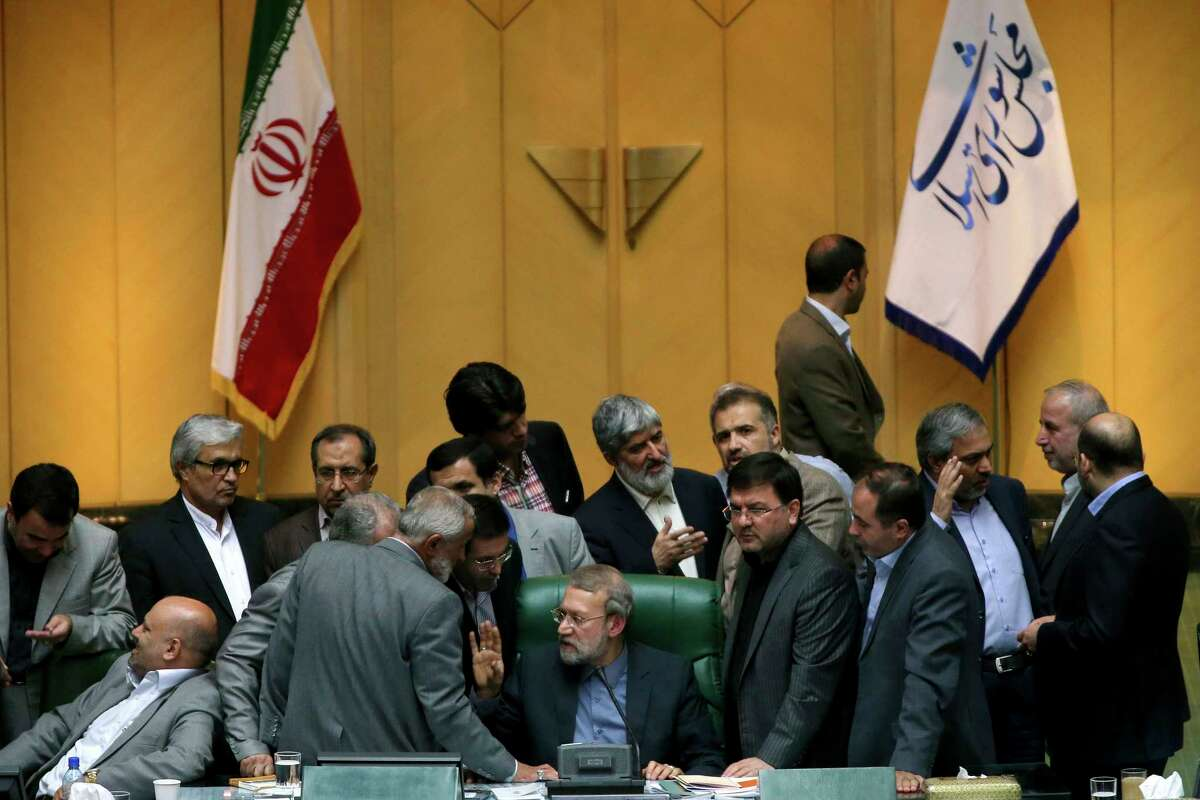 In this photo taken on Sunday, Oct. 11, 2015, Iran's parliament speaker Ali Larijani, center, speaks with lawmakers in an open session of parliament while discussing a bill on Iran's nuclear deal with world powers, in Tehran, Iran. Iran's parliament voted Tuesday to support implementing a landmark nuclear deal struck with world powers despite hard-line attempts to derail the bill, suggesting the historic accord will be carried out.