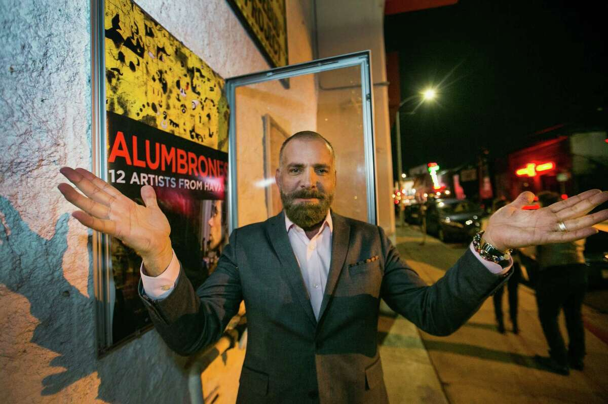 """Cuban producer Fermin Rojas poses with the poster of his film, """"Alumbrones,"""" Spanish for """"illuminations,"""" before its opening at the Arena Cinema Hollywood in Los Angeles. When Rojas wanted to make a documentary profiling 12 Cuban artists living in and around Havana, he used a Canadian production company and a cultural license to film on the island. Rojas is already at work on a second documentary, this one about a gay men's choir in Havana."""