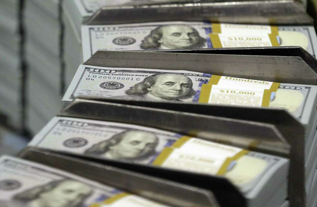 In this Sept. 24, 2013 photo, freshly-cut stacks of $100 bills make their way down the line at the Bureau of Engraving and Printing Western Currency Facility in Fort Worth, Texas. The number of people around the world worth $1 million or more hit a record 14.6 million in 2014 as rising stock prices lifted the value of personal wealth in a few key countries, according to a report released Wednesday, June 17, 2015, from consultant Capgemini and RBC Wealth Management. Much of the gain came in the U.S. where a broad index of stocks, the Standard and Poorís 500, rose 11 percent last year.