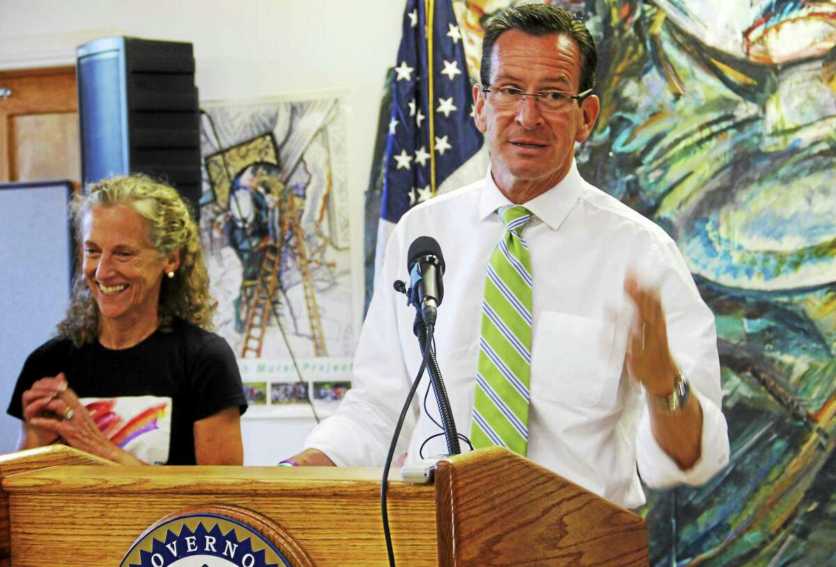 Gov. Dannel Malloy talks about the American Mural Project next to the project's leader, Ellen Griesediesk, in this 2014 file photo from Winsted. Malloy said the state could offer a $1 million matching grant if the project is able to raise $1.4 million.