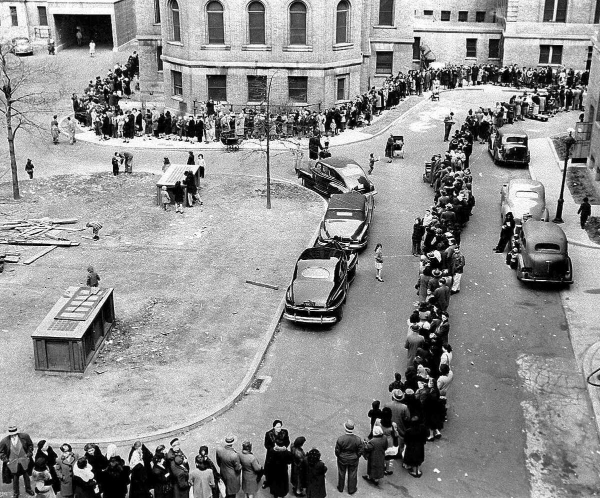 In this April 14, 1947 file photo, a long line winds toward the entrance to Morrisania Hospital in the Bronx borough of New York, where doctors are inoculating against smallpox. In an attempt to halt the spread of the disease, officials said city residents were being vaccinated at the rate of eight a minute. (AP Photo/File)