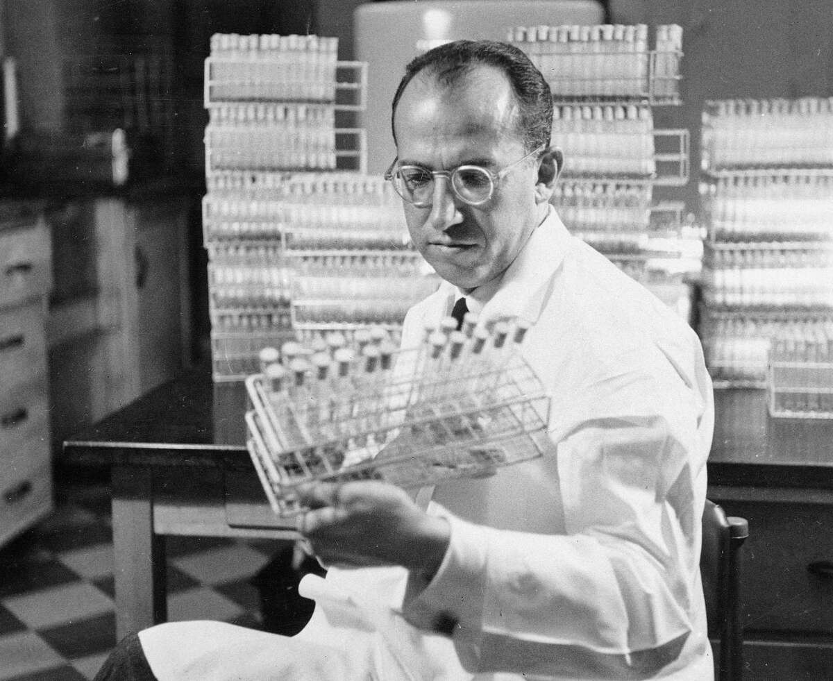 FILE - In this Oct. 7, 1954 file photo, Dr. Jonas Salk, developer of the polio vaccine, holds a rack of test tubes in his lab in Pittsburgh, Pa. (AP Photo/File)