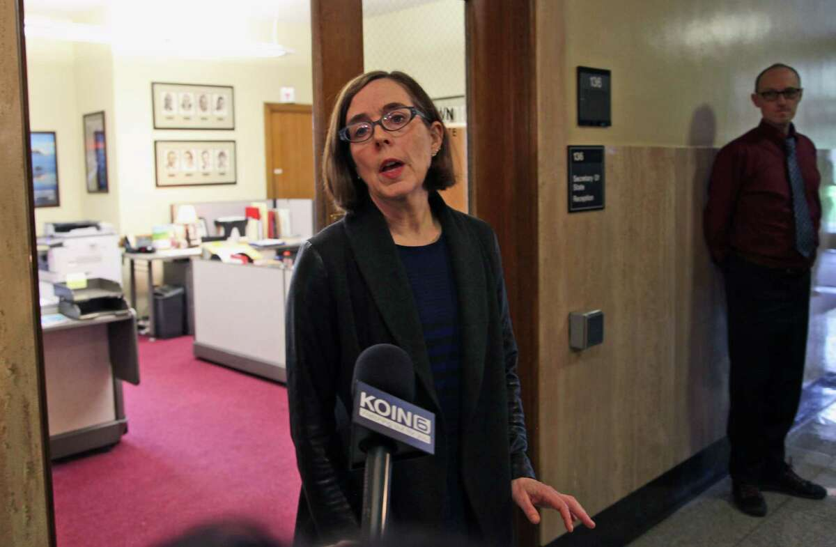 Oregon Secretary of State Kate Brown speaks to the media outside of her office at the Oregon Capitol in Salem, Ore., on Friday, Feb. 13, 2015. Brown will take over as governor after John Kitzhaber announced his resignation on Friday amid a growing ethics scandal involving his fiancee, a green-energy consultant accused of using her relationship with the governor to land contracts for her business. (AP Photo/Gosia Wozniacka)