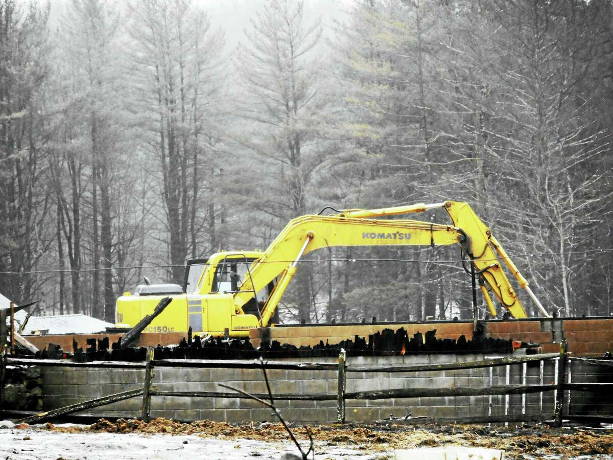 CATHERINE GUARNIERI — THE REGISTER CITIZEN An excavator clearing the remains of a barn that burned early Tuesday in Cornwall.
