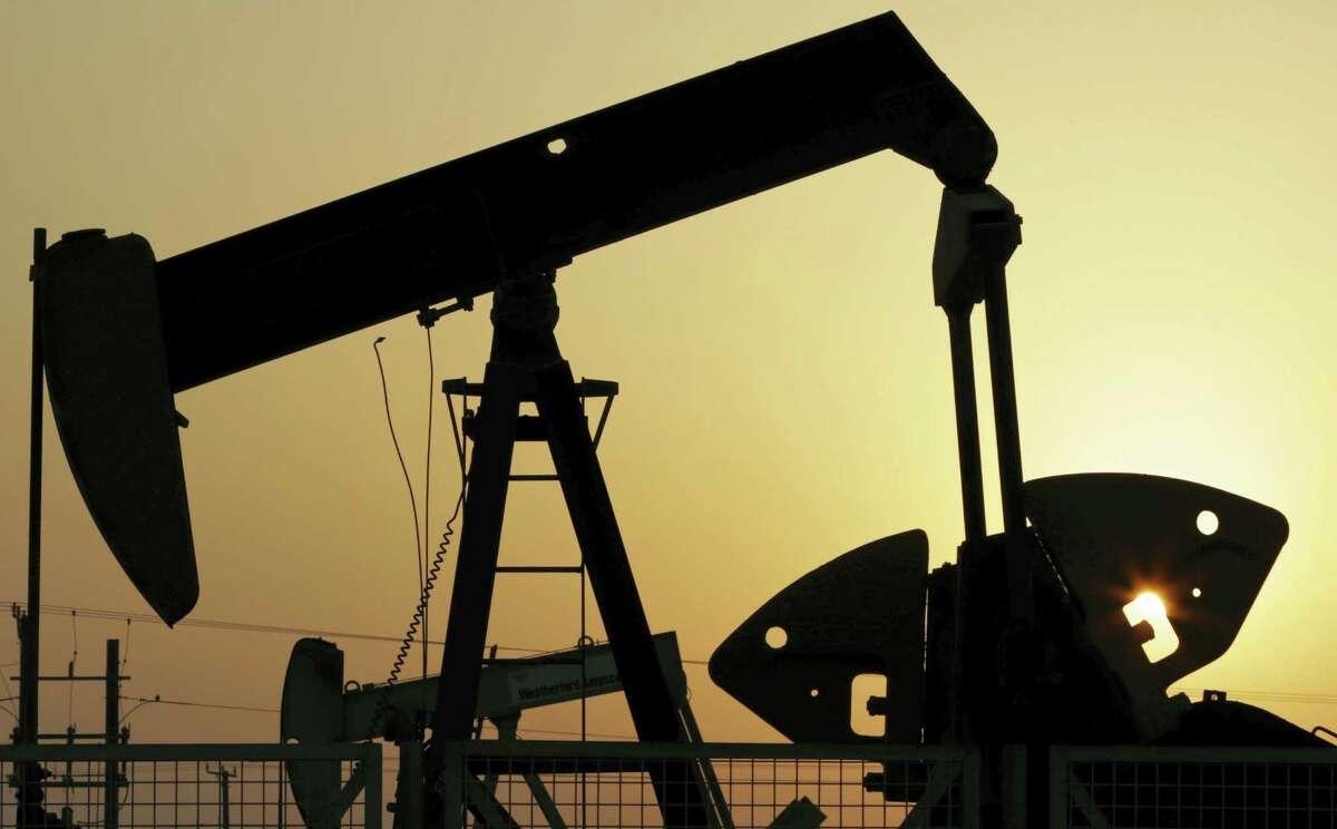 In this Sept. 30, 2015 photo, oil pumps work in the desert oil fields of Sakhir, Bahrain.