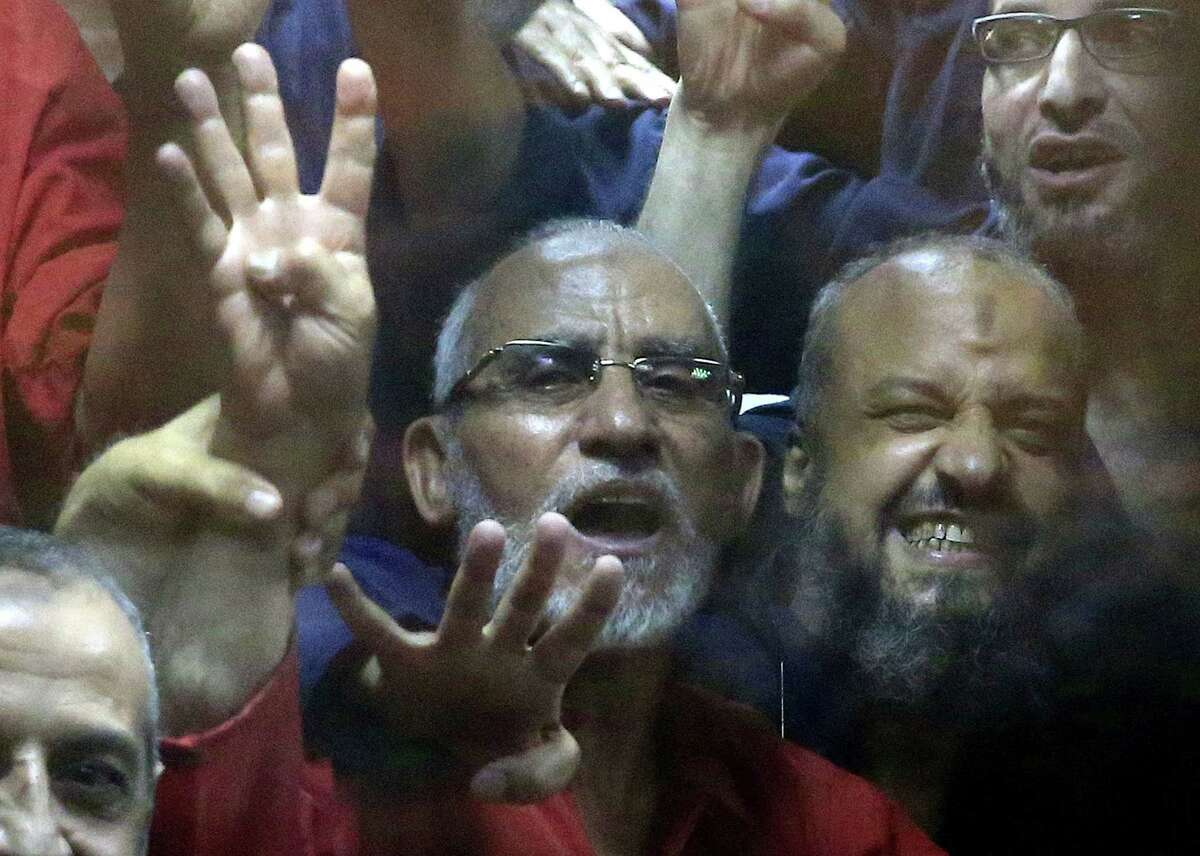 Egyptian defendants including the spiritual leader of the Muslim Brotherhood, Mohammed Badie, left, and Senior Muslim Brotherhood leader Mohammed el-Beltagy, right, make a four-fingered gesture referring to the 2013 killing of Muslim Brotherhood protesters at the Rabaah Al-Adawiya mosque, in a makeshift courtroom at the Police Academy courthouse in Cairo, Egypt, Tuesday, June 16, 2015. An Egyptian court on Tuesday confirmed a death sentence handed to ousted Egyptian President Mohammed Morsi over a mass prison break during the 2011 uprising that eventually brought him to power. The judge also confirmed death sentences for five other jailed leading members of Morsiís Muslim Brotherhood, including Badie, the groupís leader, and Saad el-Katatni, the head of its short-lived political party. (AP Photo/Hassan Ammar)