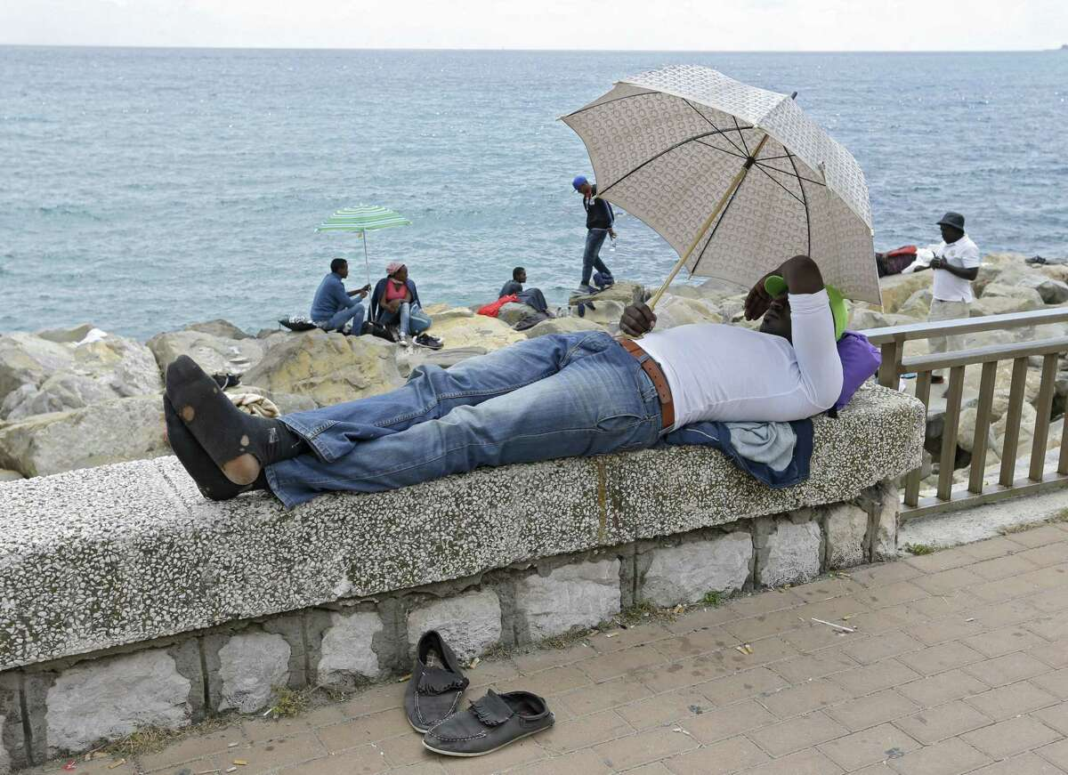 A migrant waits at the Franco-Italian border near Menton, southeastern France, Tuesday, June 16, 2015. Some 100 migrants, principally from Eritrea and Sudan, attempted since last Friday, to cross the border from Italy and have been blocked by French and Italian gendarmes. (AP Photo/Lionel Cironneau)
